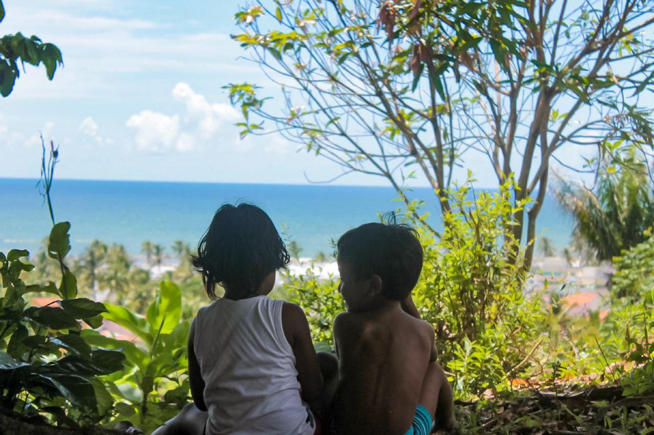 Crianças indígenas, diante da floresta e do mar em aldeia Pataxó na Bahia: integração com a natureza. Foto de Alice Pataxó