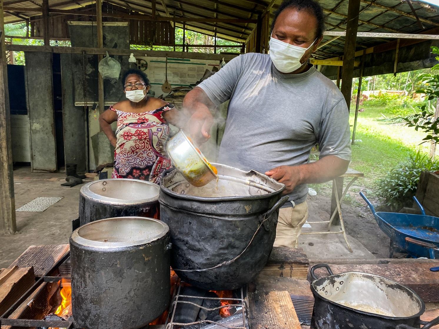 Raimundo Magno, com uma máscara médica, cozinhando pupunhas.