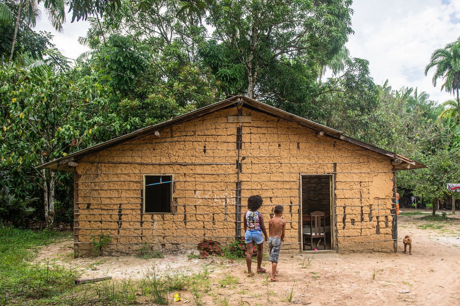 Two people and a dog in front of a house in the Abacatal Quilombola Community, in Ananindeua, Pará.