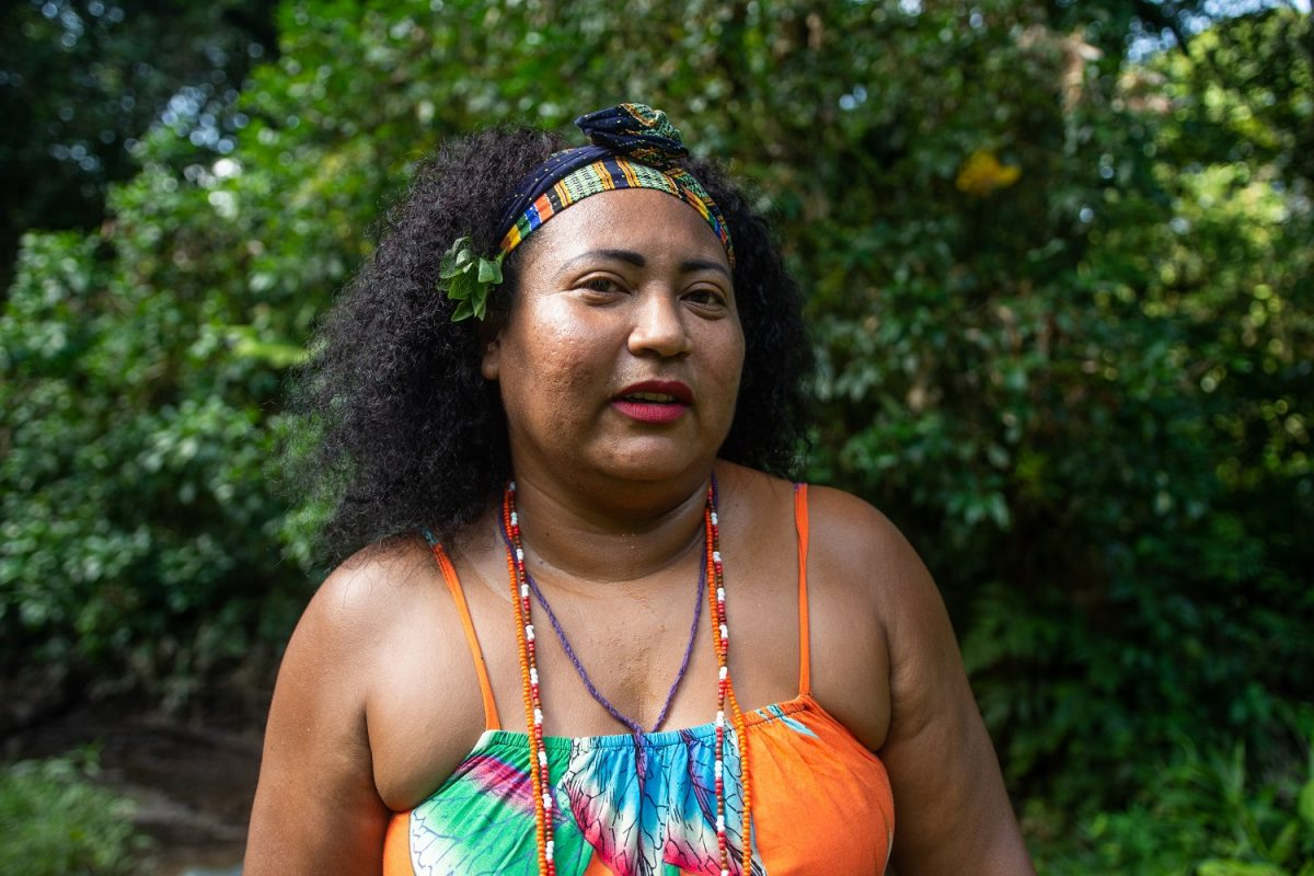 Vanuza Cardoso wears a headband, an orange top, and beaded necklaces.