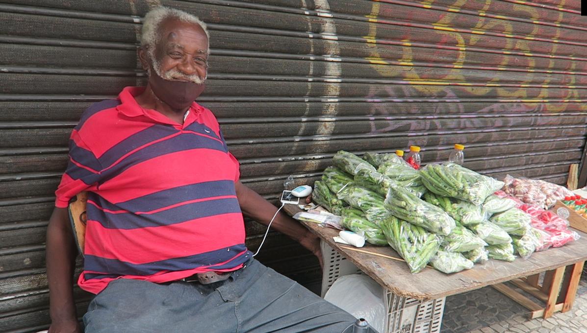 Seu Jaime sorri para a foto, ao lado dos produtos que vende diariamente na Praça Tiradentes. Foto Pedro Madeira
