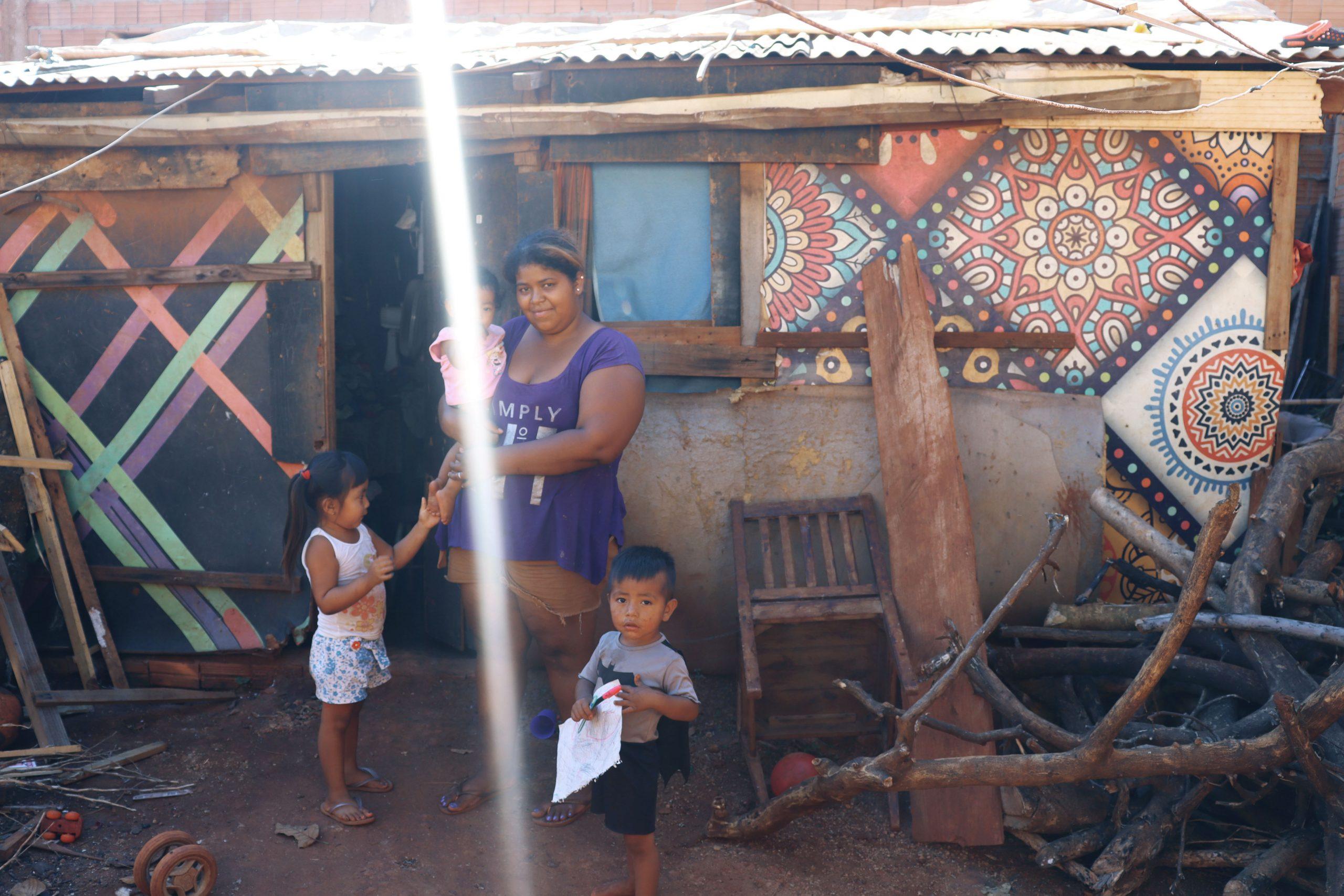 Luana com três de seus sete filhos: moradia improvisada com tapumes, telhas e pedaços de madeira. Foto Ethieny Karen