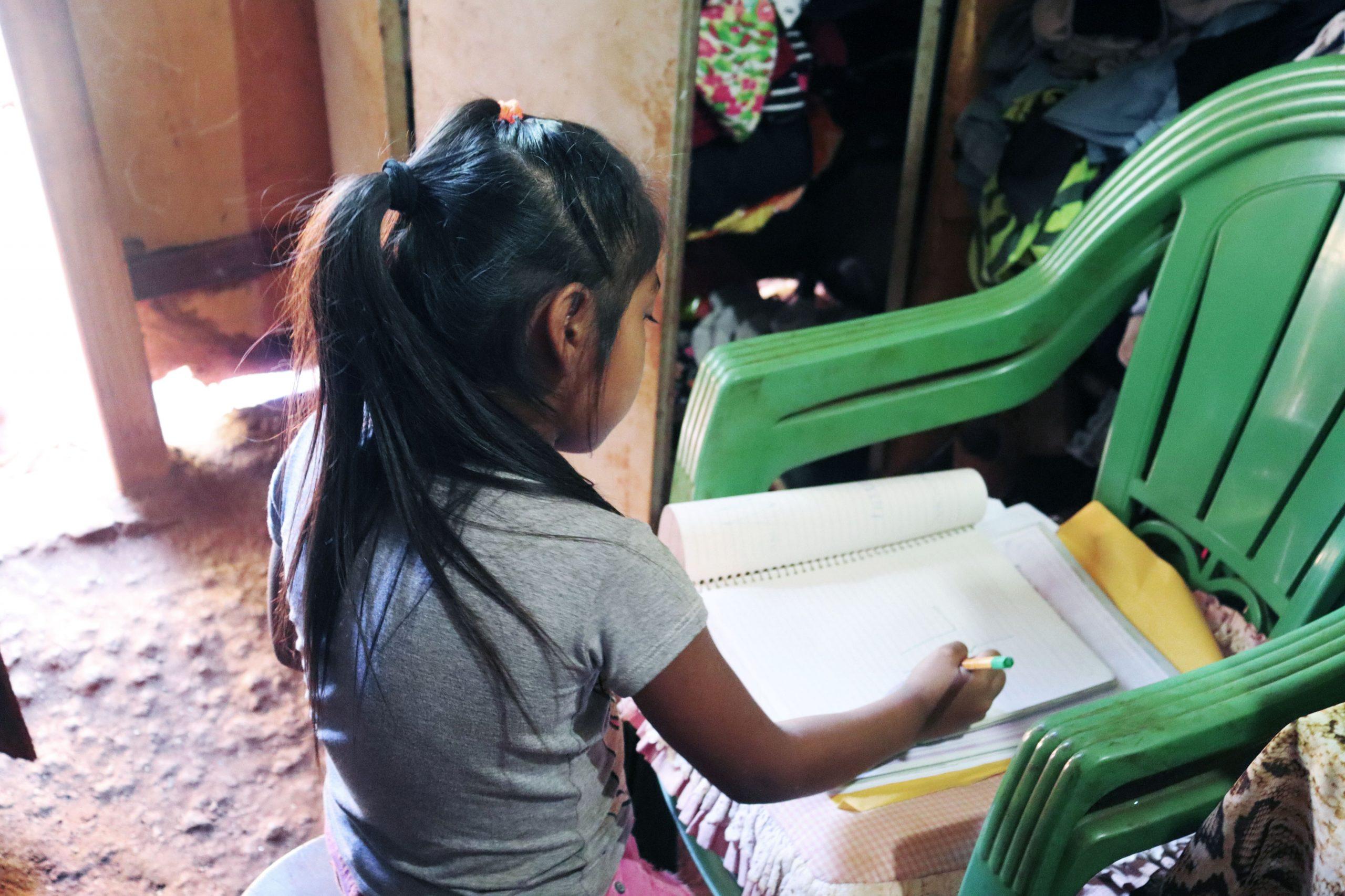 Menina Terena faz a lição em cadeira improvisada como mesa: um dos poucos cantos iluminados da casa. Foto de Ethieny Karen