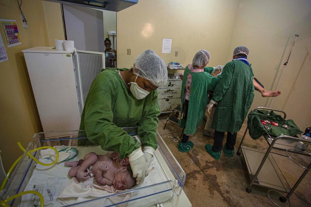 Bebê é atendido em hospital da Ilha de Marajó, no Pará, enquanto profissionais de saúde cuidam de mãe com covid-19: Brasil registrou queda da natalidade em 2020 (Foto: Tarso Sarraf / AFP - 13/06/2020)