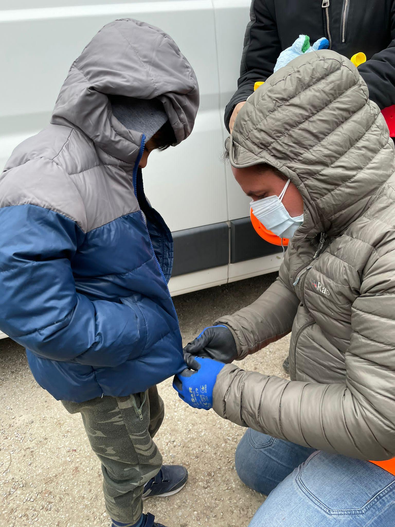 Jornada pela Bósnia: voluntário veste jaqueta em criança no campo de Hadžići. Foto Janaina Cesar