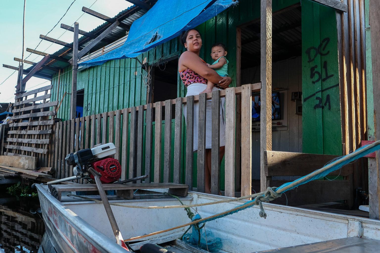 Pâmela Gomes com o filho em sua casa no bairro do Educandos, em Manaus: sofrimento com as cheias recorrentes desde o ano de 2012 (Foto: Alberto César Araújo/Amazônia Real)