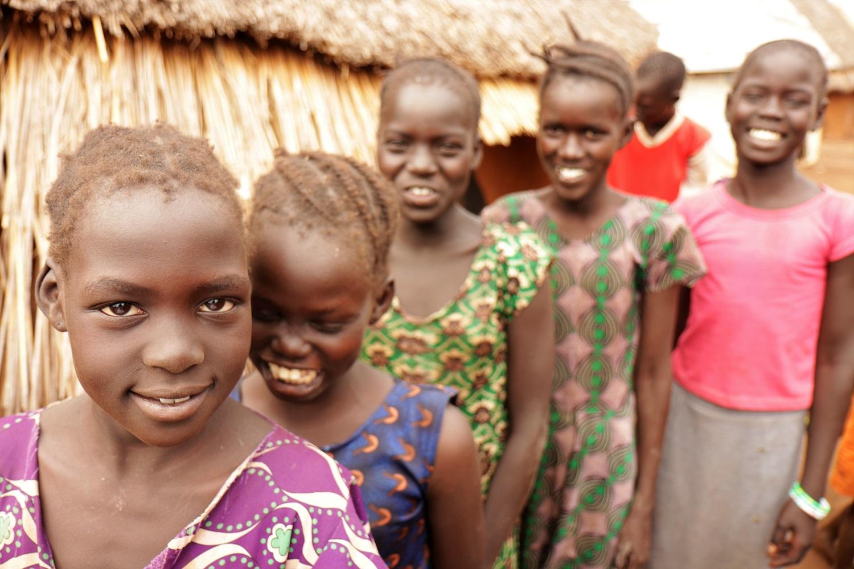 Crianças refugiadas do Sudão do Sul brincam no campo de Nguenyyiel sob a supervisão de vizinhos, enquanto seus pais visitam o ponto de distribuição de alimentos. Foto ACNUR. Setembro/2020