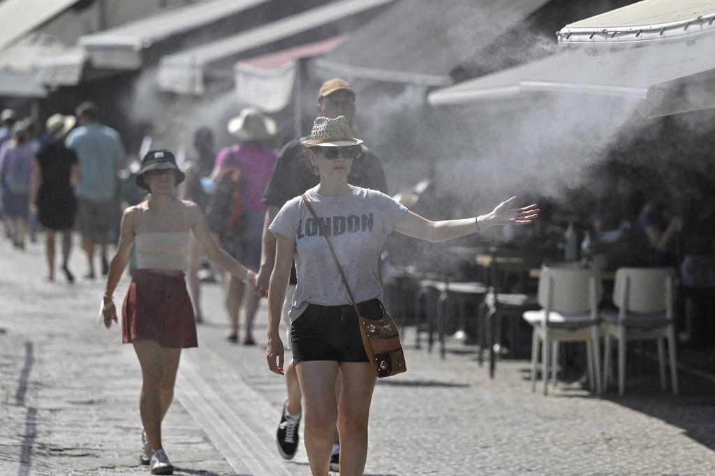 Turistas aproveitam spray de água para enfrentar o calor em Atenas: temperatura na Grécia alcançou 44 graus (Foto: Louisa Gouliamaki / AFP - 29/07/2021)
