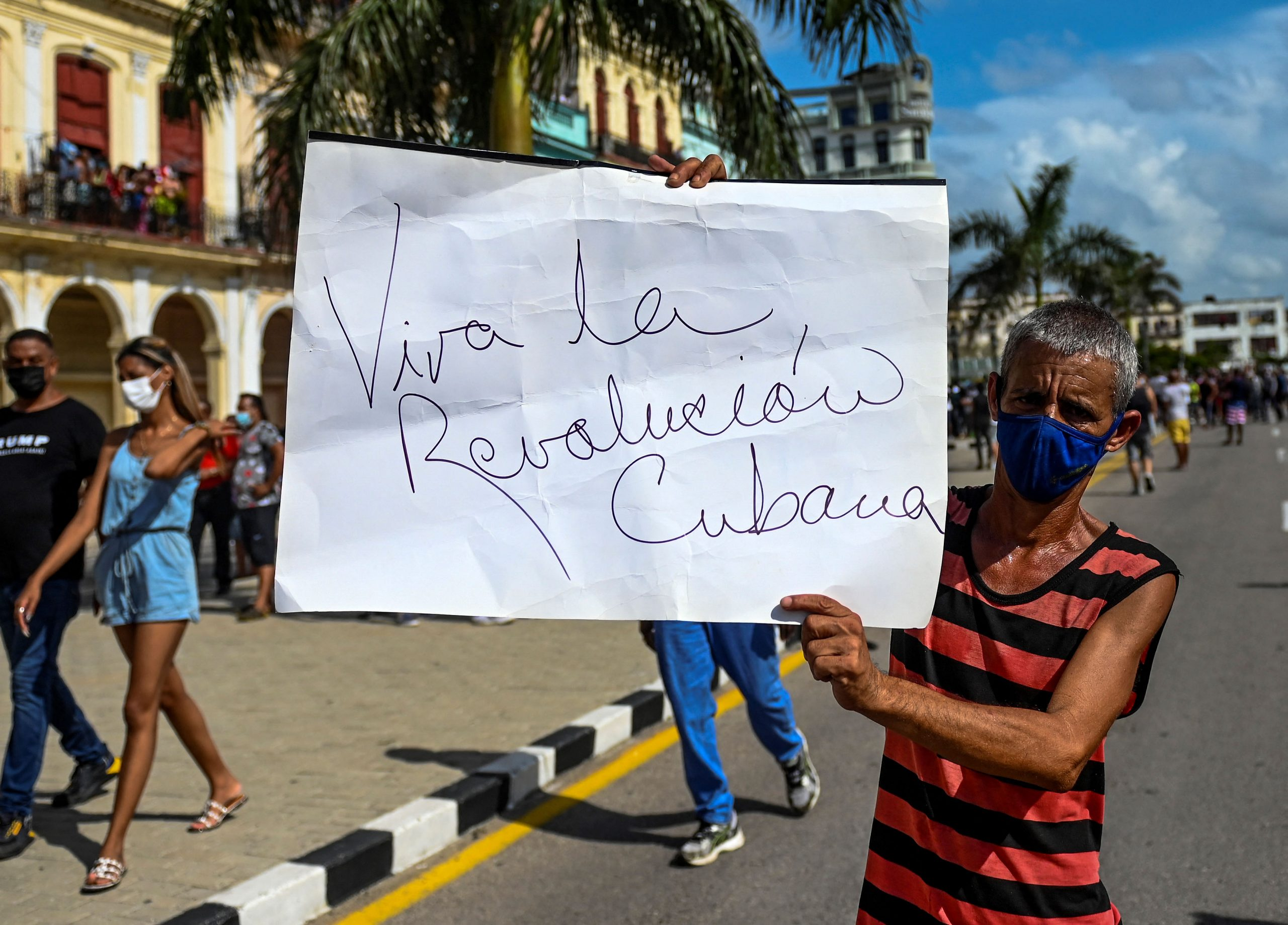 """Defensor do governo de Miguel Diaz-Cnal ergue o cartaz com a frase histórica: """"Viva a revolução cubana!"""" Foto Yamil Lage/AFP"""