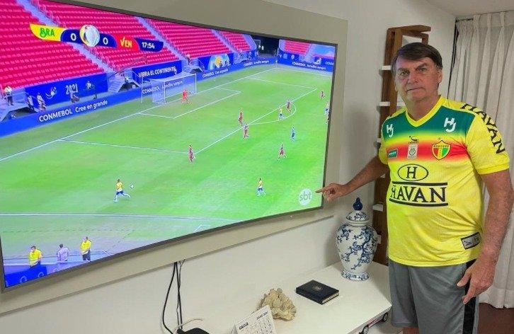 Jair Bolsonaro com camisa do Brusque e jogo do Brasil na TV: Havan, do empresário bolsonarista Luciano Hang, patrocina o time catarinense (Foto: Reprodução/Twitter)