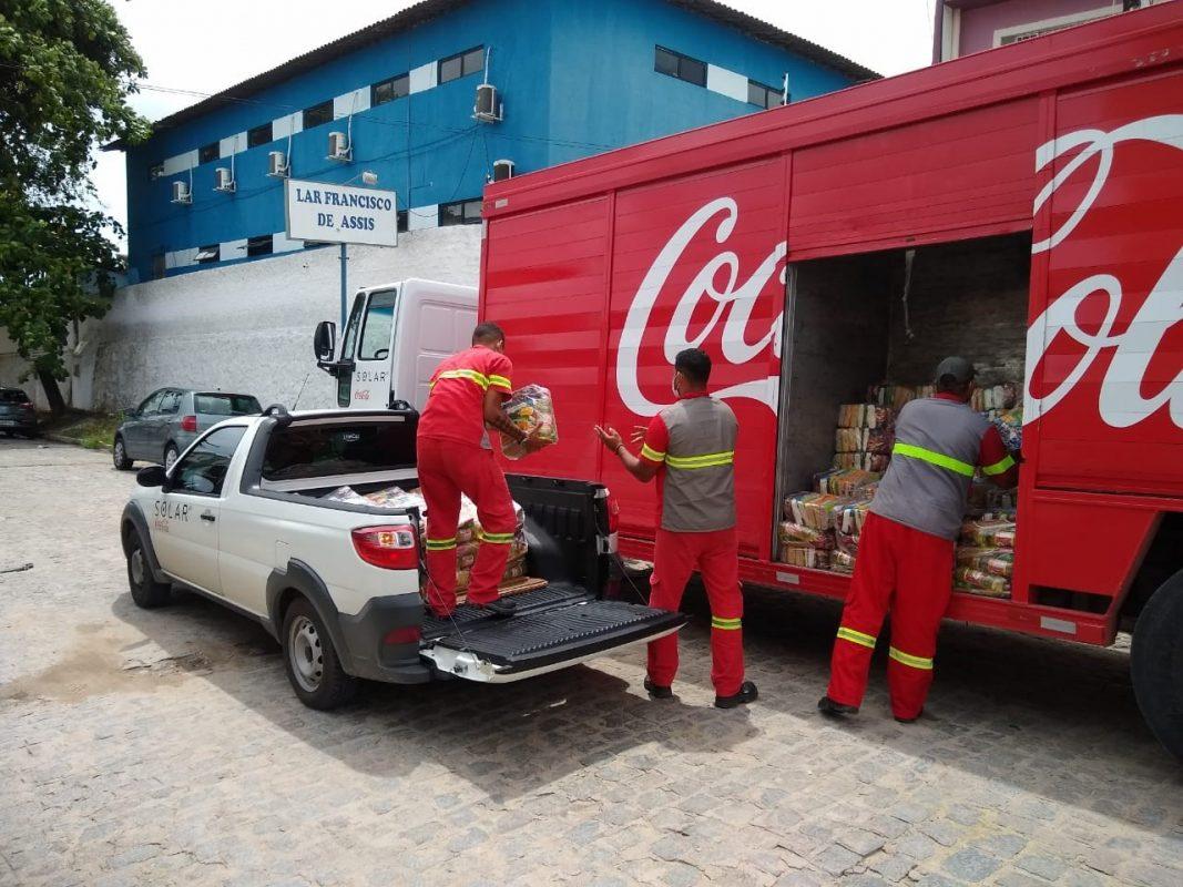 Três funcionários uniformizados da Coca-Cola Brasil transportam cestas básicas, movendo-as de uma picape branca, posicionada à esquerda, para o caminhão vermelho da Coca-Cola que está no canto direito.