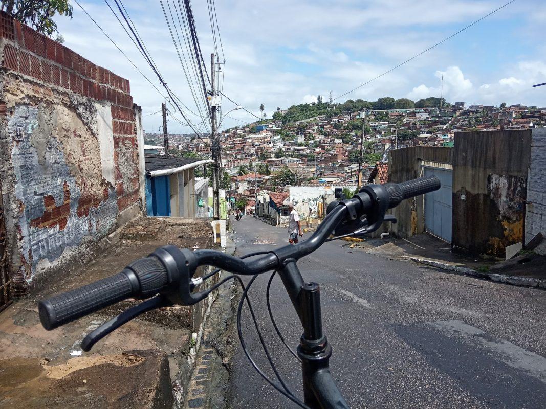 Guidão da bicicleta do repórter, em primeiro plano, com um morro de Olinda ao fundo