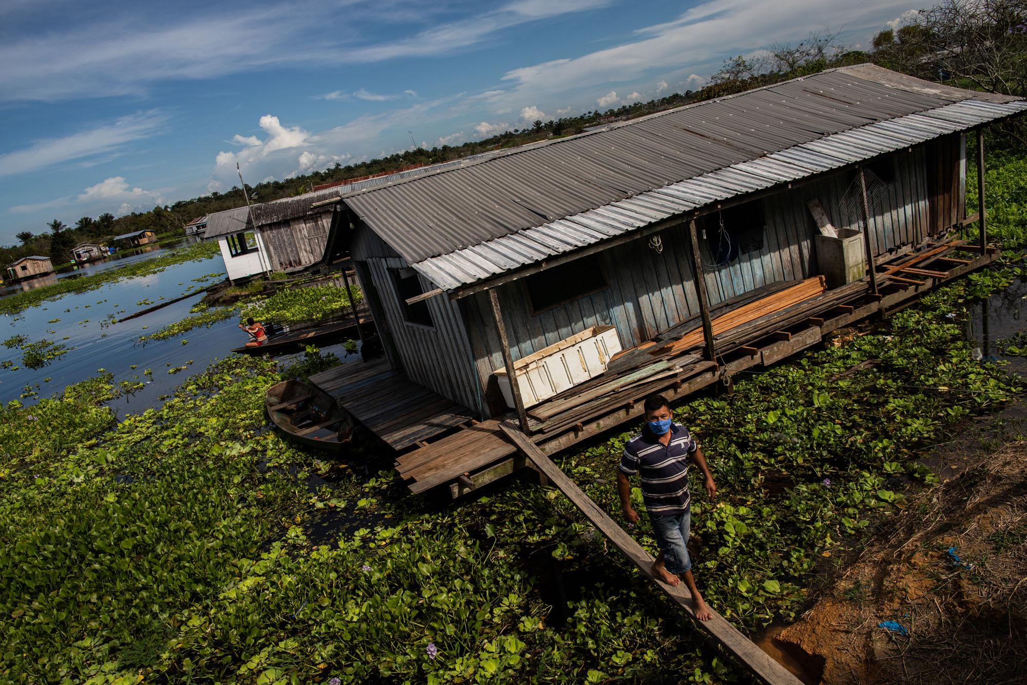 """Em Iranduba (AM), Dedé Batista Pinto caminha sobre uma viga de madeira ao deixar sua sua residência flutuante na vila do Cacau Pirêra: """"Final do mês passado mesmo eu matei uma cobra dentro de casa"""" (Foto: Raphael Alves/Amazônia Real)"""