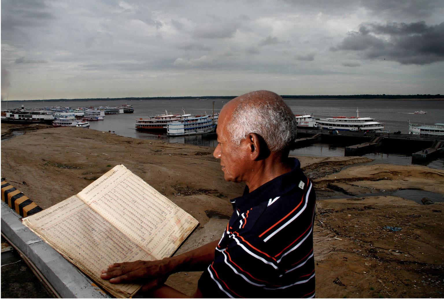 Valderino Pereira, em foto de antes da pandemia no período da seca, mostra o livro de registro diário da medição do rio Negro (Foto: Alberto César Araújo/Amazônia Real)