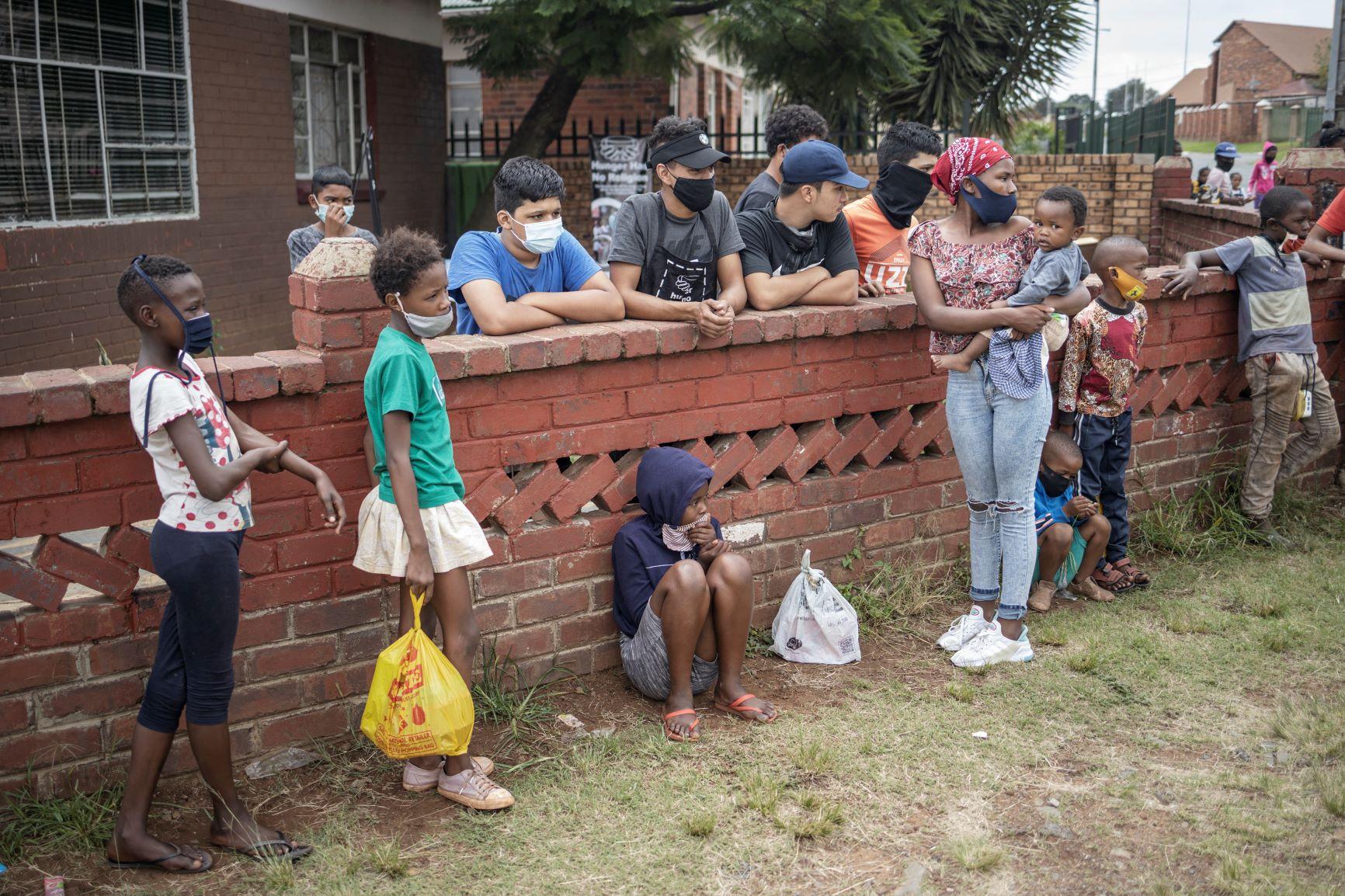 Crianças e adolescentes em fila para receber comida em Johannesburgo, África do Sul: pandemia aumento em 40% número de pessoas em insegurança alimentar aguda (Foto: Michele Spatari / AFP - 26/02/2021)