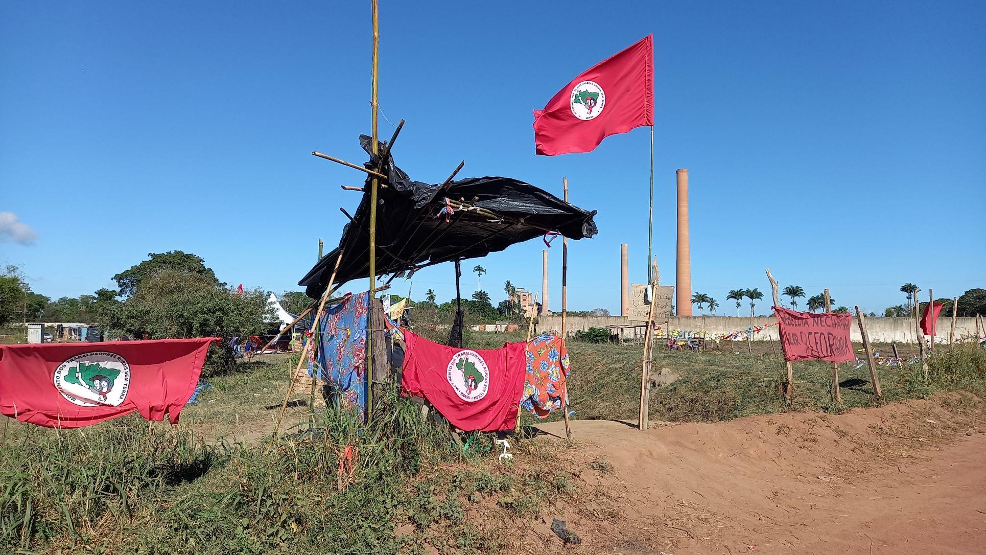 Bandeiras do MST na entrada do acampamento em Campos: luta por ocupação e destinação das fazendas para a reforma agrária (Foto: Vivi Fernandes de Lima)