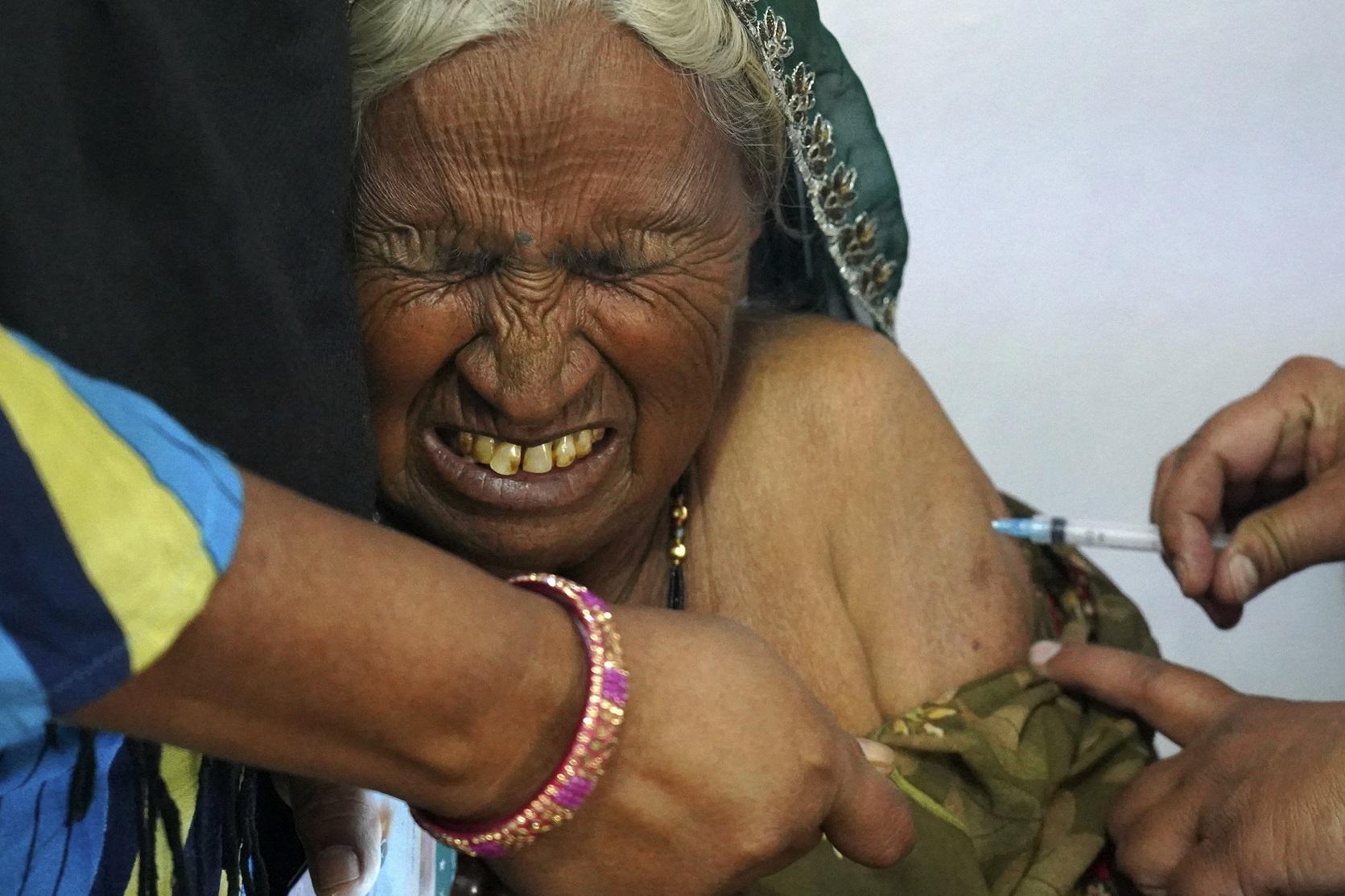 Nos arredores de Ajmer, na Índia, idosa recebe a sua dose da vacina contra a covid-19. Foto Himanshu Sharma/AFP. Março/2021