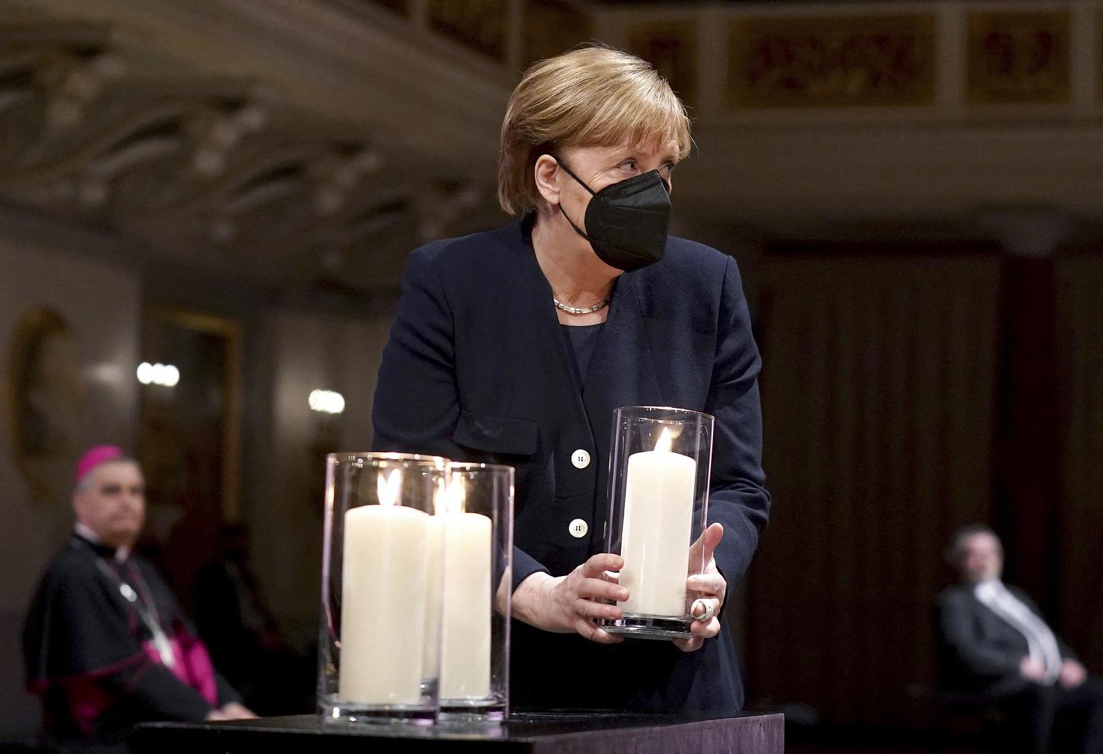 A chanceler alemã, Angela Merkel, segura uma vela durante uma cerimônia em homenagem às vítimas da pandemia. Foto Michael Sohn/Pool/AFP. Abril/2021