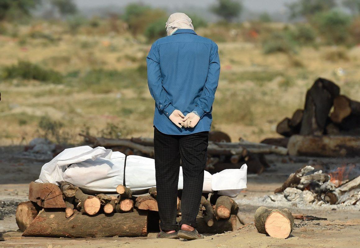 Em um campo de cremação, em Allahabad, na Índia, parente chora ao lado do corpo de seu ente querido que morreu devido à Covid-19. Foto Sanjay Kanojia/AFP. Maio/2021