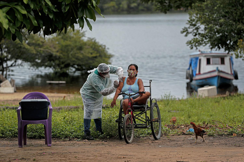 Agente de saúde da Secretaria de Saúde Indígena administra uma segunda dose da vacina contra a covid-19 em uma mulher da aldeia Esperança do Rio Arapiun, no Baixo Amazonas, no Pará. Foto Tarso Sarraf/AFP. Fevereiro/2021