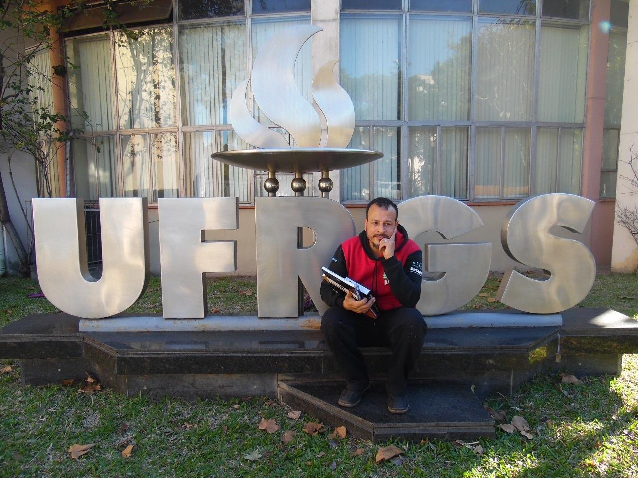Alexandro na porta universidade com o seu livro recém-lançado. Foto Vinicius Cardoso